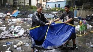 Ativistas tentam recuperar uma barraca destruída pela polícia durante a madrugada na praça Bolívar, em Caracas.
