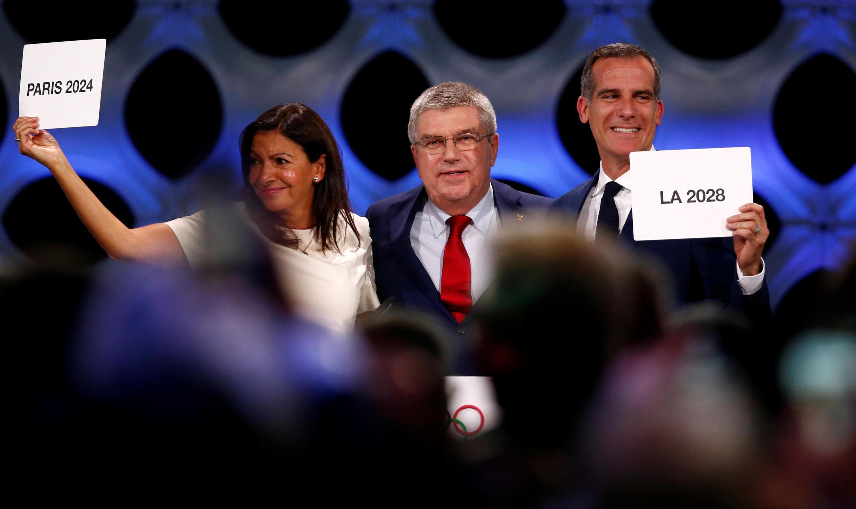 A prefeita de Paris, Anne Hidalgo, Thomas Bach, presidente do Comitê Olímpico Internacional (COI), no centro, e à direita o prefeito de Los Angeles, Eric Garcetti, em 13 de setembro de 2017.