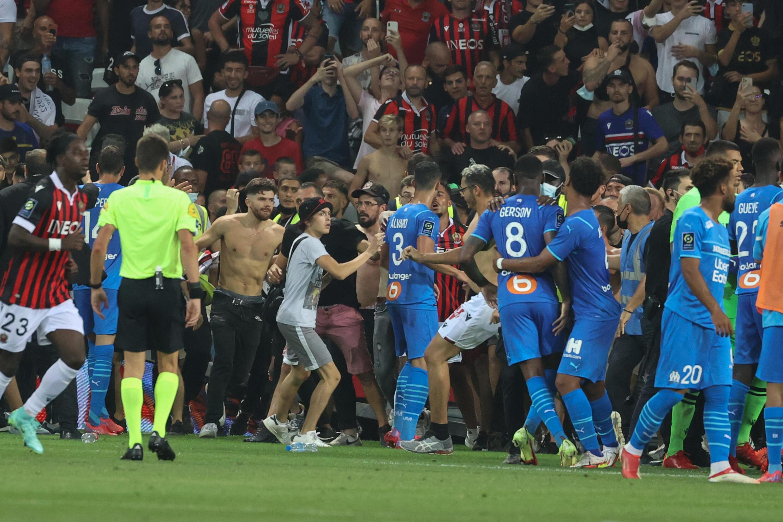 Des supporters envahissent le terrain lors du match de Ligue 1 Nice-Marseille après d'une bouteille en plastique a été lancée sur le joueur marseillais Dimitri Payet, le 22 août 2021 à Nice