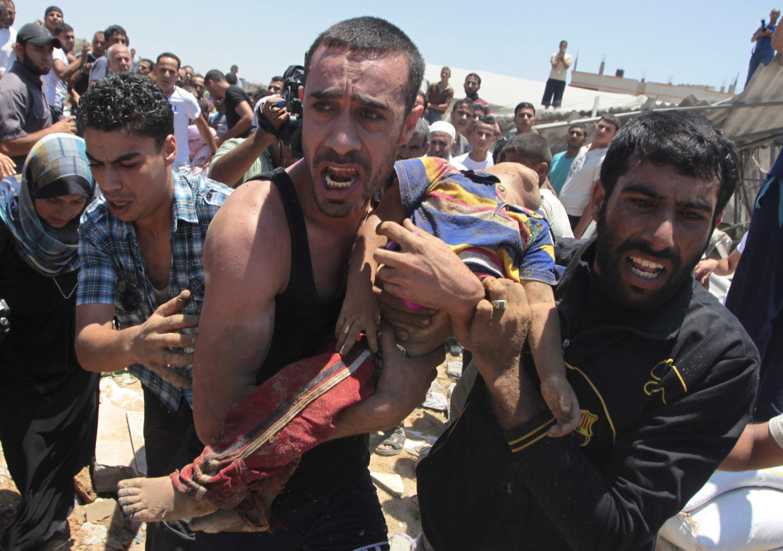 Des habitants de la ville de Gaza portent le corps d'un enfant, mort dans un bombardement aérien, selon les autorités médicales palestiniennes, le 9 juillet 2014.