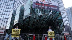 """Militantes de Greenpeace cualgan una pancarta que dice: """"Total, una amenaza oficial para el arrecife amazónico"""". Francia, 27 de marzo de 2017."""