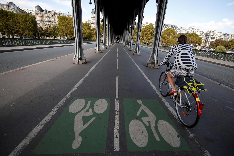 A woman rides a bicycle on the Pont de Bir-Hakeim bridge in Paris, France.