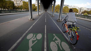 A woman rides a bicycle on the Pont de Bir-Hakeim bridge in Paris, France.