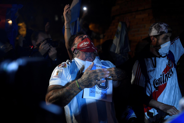 Um torcedor de futebol segura firmemente uma placa número 10 durante uma homenagem à lenda do futebol argentino Diego Maradona em Barcelona no dia 26 de novembro de 2020, um dia após sua morte.