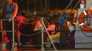 African immigrants sit on the deck of a patrol boat of Malta Maritime Squadron in Valletta, 9 November, 2012