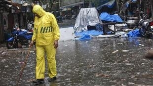 A policeman kept guard in the rain at the site of an explosion near the Opera House in Mumbai on 14 July 2011.