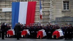 Christophe Castaner, Ministro do Interior de Rench, presta homenagem diante dos caixões de três agentes da polícia e de um funcionário administrativo, durante uma cerimónia em honra deles.