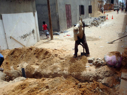 Des ouvriers ensevellissent les nouvelles canalisations.