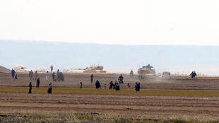 Civiles sirios  con tanques turcos que se perciben atrás avanzan en la ciudad de Kilis, Turquía. Septiembre 3 de 2016.