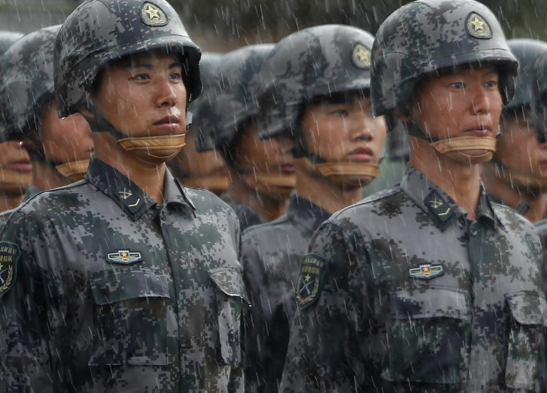 Những người lính Trung Quốc đóng tại căn cứ không quân Shek Kong ở Hồng Kông chờ đợi tiến hành diễu binh dưới trời mưa nặng hạt, ngày 29/06/2012.