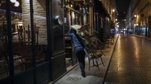 Un restaurateur ferme son établissement alors que l'heure du couvre-feu de 21h approche, le 17 octobre 2020, à Paris.