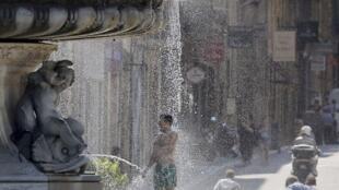 Para fugir do calor de 40°C, homem se refresca em uma fonte pública