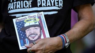 Un miembro de la Oración Patriótica con un retrato dibujado del activista de extrema derecha asesinado el 6 de septiembre de 2020 en Vancouver.
