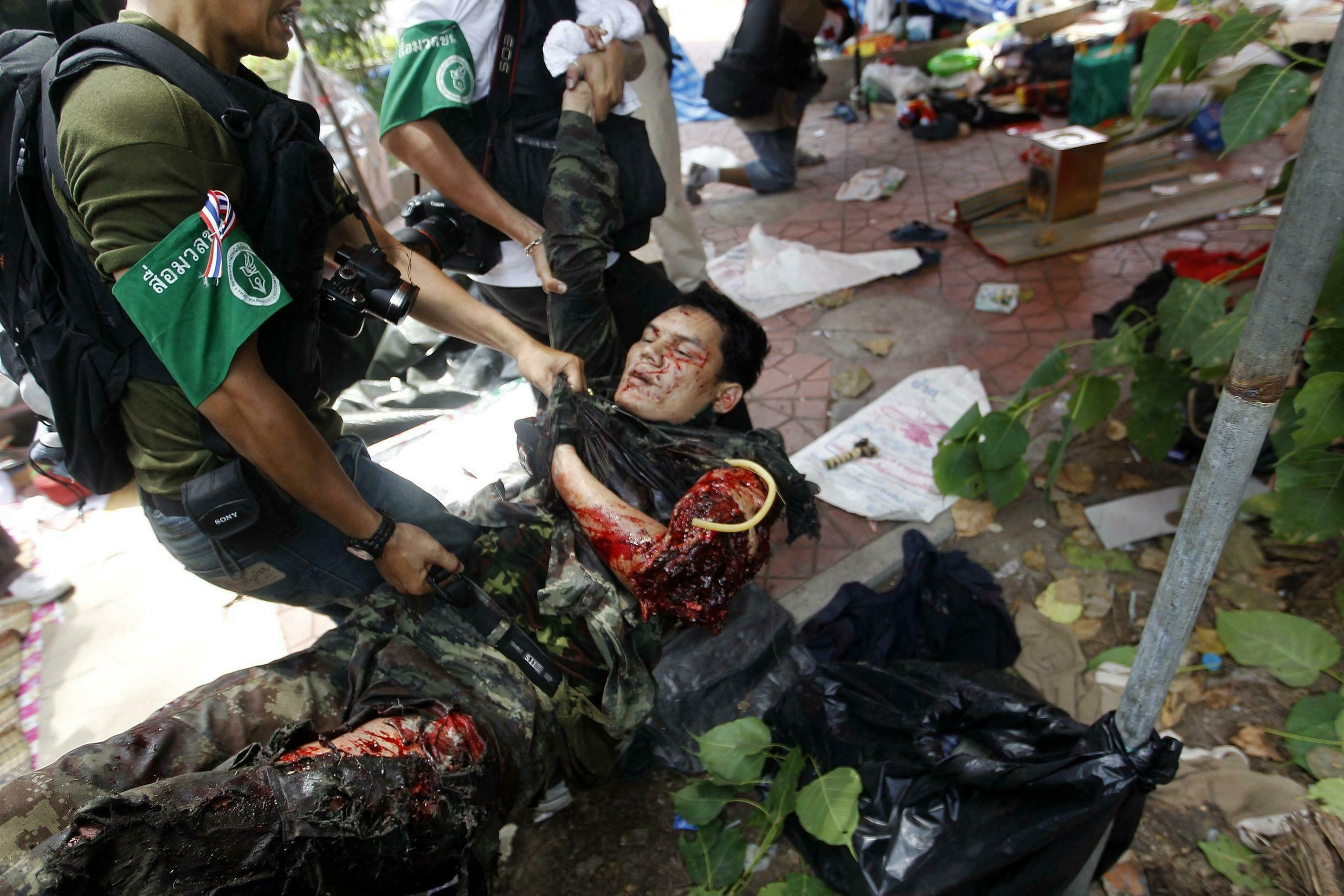 Journalists carry a badly wounded Thai soldier