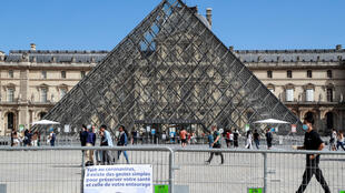 People wearing face masks walk past the Louvre Pyramid in Paris