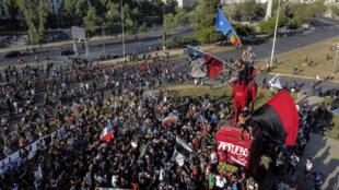 Vista aérea de manifestantes con banderas indígenas chilenas y mapuches durante una protesta contra el gobierno del presidente chileno Sebastián Piñera en la cima del monumento al General Baquedano -pintado en rojo- en la Plaza Italia, en Santiago, el 16 de octubre de 2020.