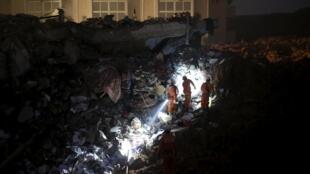 山體滑坡後,深圳工業園區的倒塌建築廢墟內,消防隊員在搜索倖存者,中國深圳,2015年12月20日。