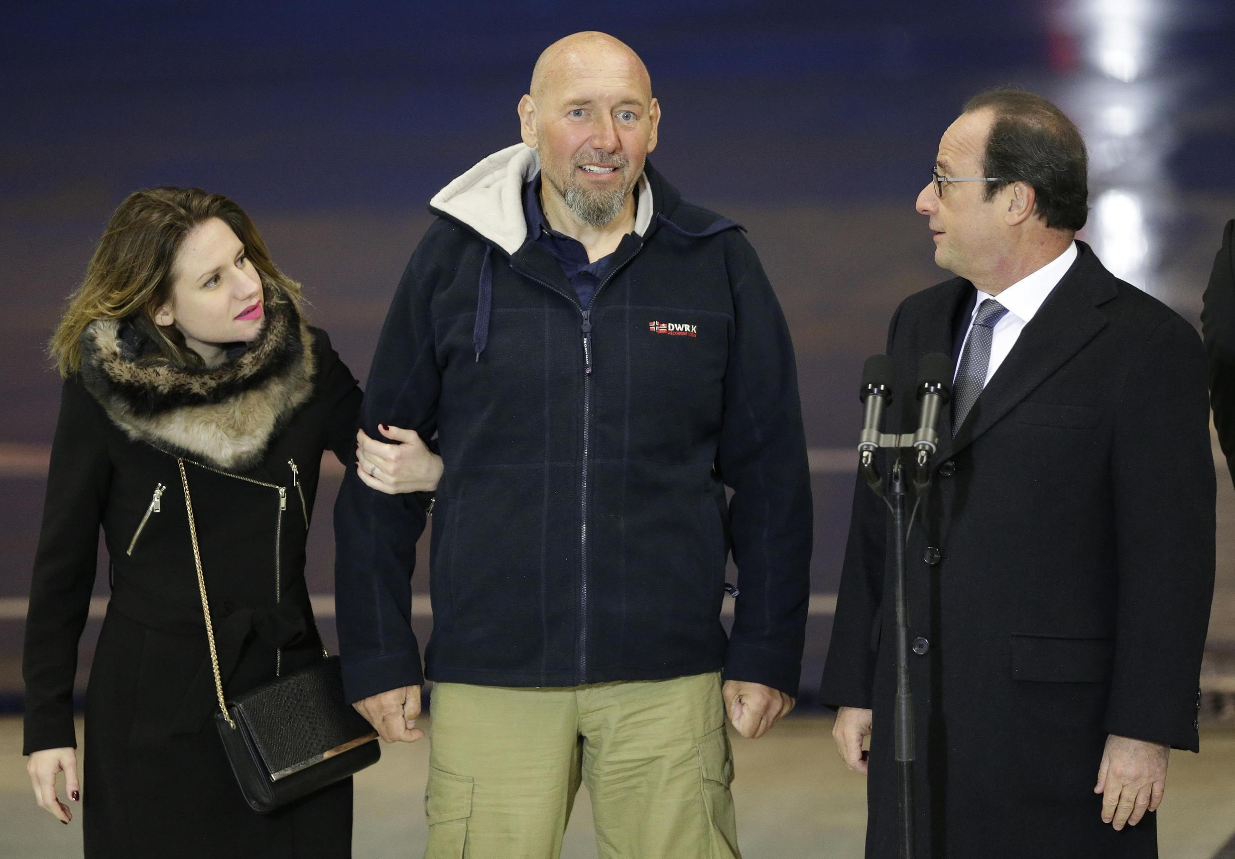 Serge Lazarevic (L) with French Defence Minister Jean-Yves Le Drian (C) with his daughter Diane (L) and French President François Hollande at Villacoublay airport