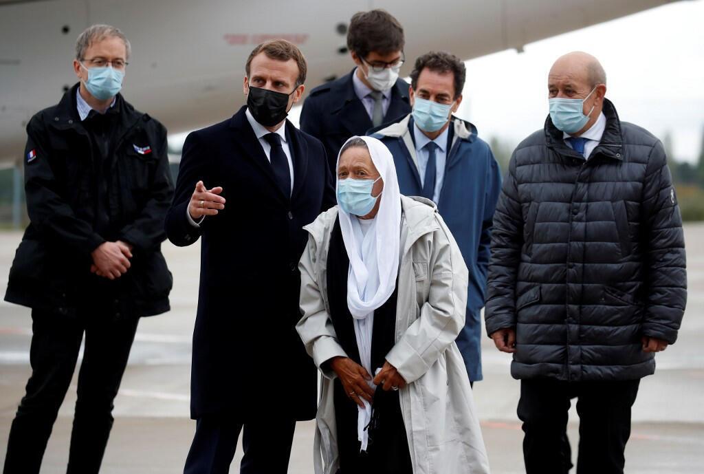 L'ex-otage française Sophie (C) à son arrivée sur le sol français entourée du président E.Macron (G) et du ministre Le Drian (D).