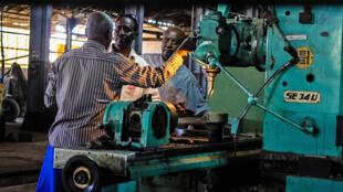 Dans l'immense hangar du dépôt, quelques ouvriers s'activent sur de vieilles machines-outils françaises.