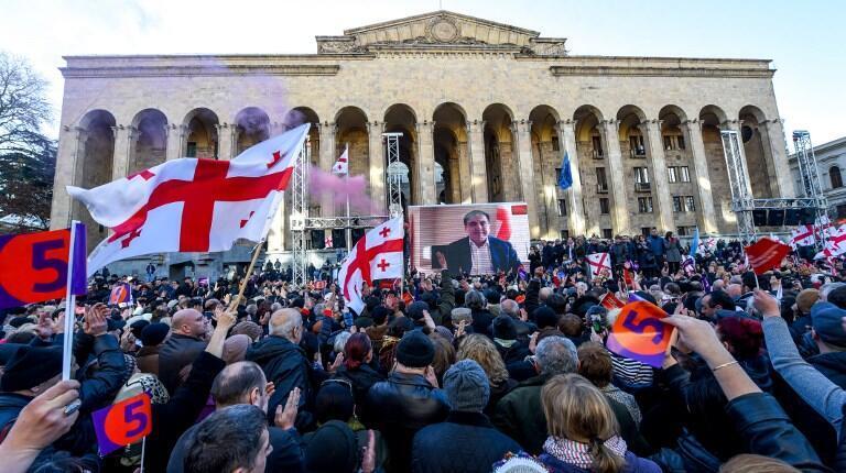 Les manifestants brandissent des drapeaux géorgiens et écoutent le message de l'ancien président Mikheïl Saakachvili qui s'adresse à eux depuis son exil aux Pays-Bas, le 2 décembre 2018, à Tbilissi.