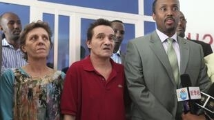 Released South African hostages Bruno Pelizzari (C) and Debbie Calitz (L) are presented by Somalia's Minister of Defence Hussein Arab Isse (R)