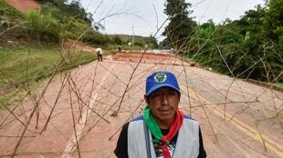Un homme se tient près d'une barricade bloquant la route panaméricaine, dans le département colombien de Cauca, le 17 mars 2019.