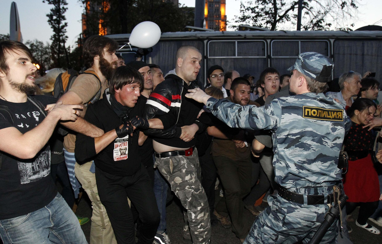 """Сотрудник ОМОНа пытается преградить дорогу протестующим, перешедшим после разгона лагеря на Чистых Прудах на """"Баррикадную"""""""