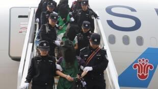 肯尼亚驱逐的涉嫌欺诈人员在警方护送下抵达北京 2016年4月13日