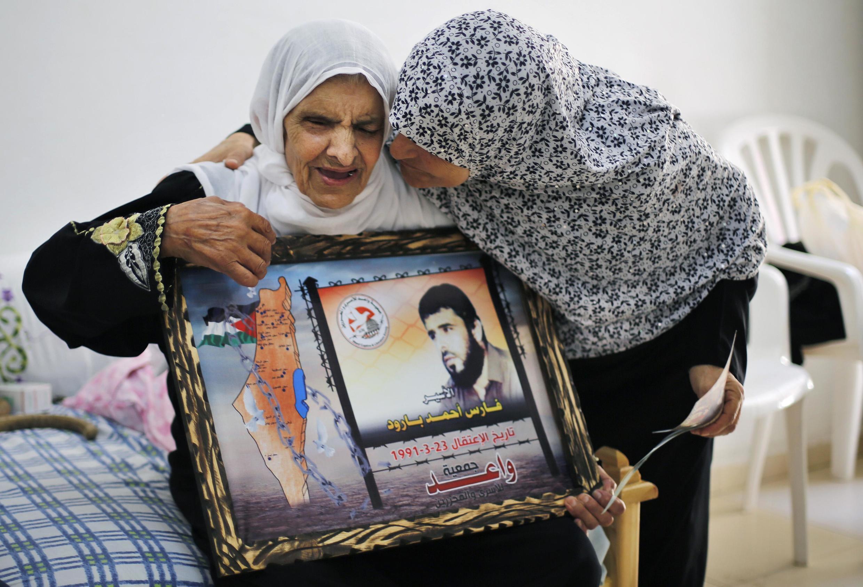 Một bà mẹ người Palestine vui mừng khi nghe tin con trai (trong ảnh) có thể được Israel trả tự do.