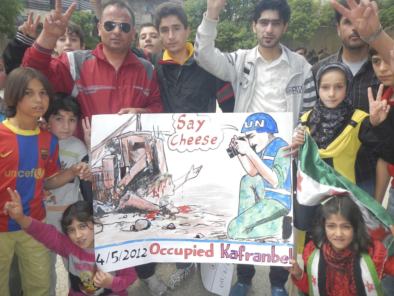 """Манифестанты в Идлибе с плакатом, где изображен наблюдатель ООН с фотоаппаратом, говорящий жертве обстрела: """"Скажите cheese!"""""""