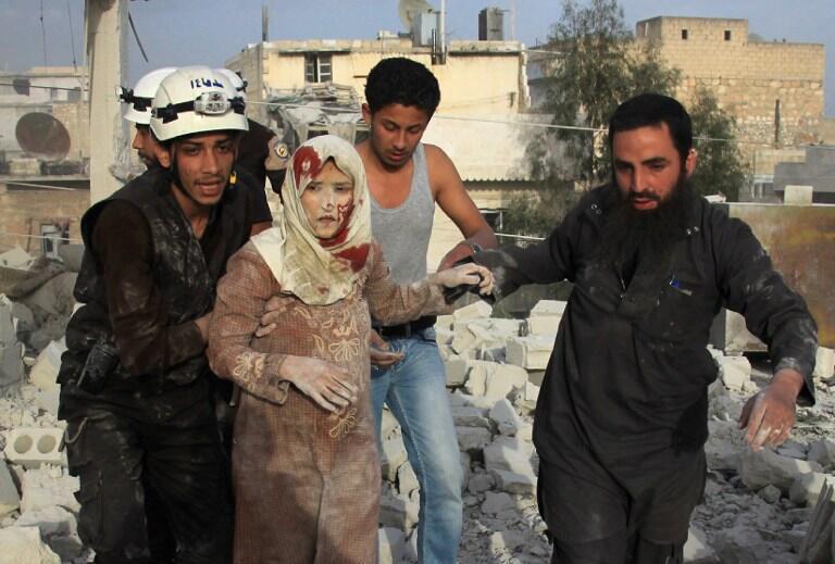Maafisa wa Idara za huduma za dharura wakimsaidia mwanamke kukimbia mashambulizi ya anga ya jeshi la Syria, kaskazini mwa Aleppo (Haydariya), Aprili 10, 2016.