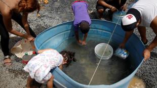 Moradores enchem recipientes com água em uma área atingida pelo furacão Maria em Canovanas, em Porto Rico.