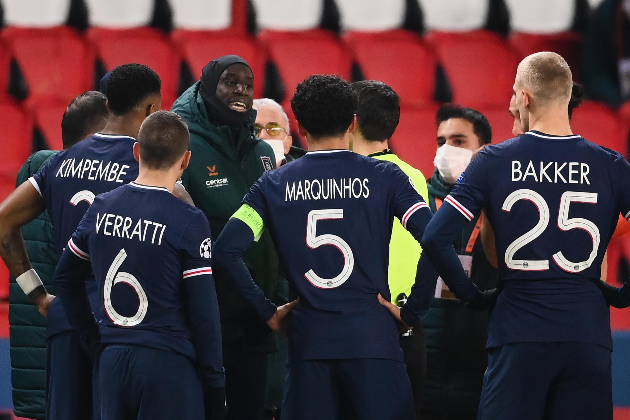 El atacante francés el Basaksehir Demba Ba (izq, de frente) habla con el árbitro luego de la suspensión del partido del grupo H de la Champions contra el PSG por un incidente denunciado como racista del cuarto árbitro en el Parque de los Príncipes