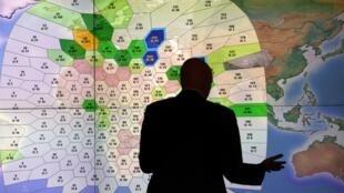 Funcionário da Inmarsat, companhia inglesa de comunicações por satélite, verifica tela com indicações de pilotos numa tentativa de traçar a posição da aeronave da Malaysia Airlines.