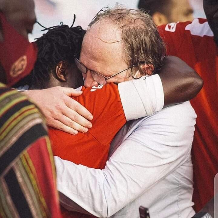 The Gambia Scorpions football coach Tom Sainfeit hugging a player after the team qualified for CAN
