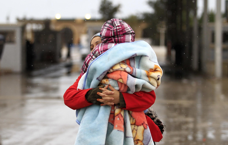 Túnez:  en el puesto fronterizo de Ras Jedir, entre Libia y Túnez, una mujer tunecina con su niño en brazos deja atrás la violencia en Libia, el  23 de febrero de 2011.