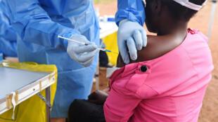 Afisa wa afya nchini DRC akitoa chanjo dhidi ya Ebola kwa mwanamke aliyewasiliana na mwathirika wa Ebola katika eneo la Mangina, Kivu Kaskazini, tarehe 18 Agosti 2018.