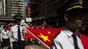 Youth uniformed group members carry a Chinese national flag during a march in the streets to demonstrate against a pro-democracy Occupy Central campaign in Hong Kong August 17, 2014.