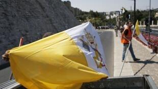 Un trabajador prepara una bandera del Vaticano para colocarla en el centro antiguo de Jerusalem, el 23 de mayo de 2014.