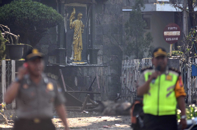 Des policiers devant l'église Santa Maria de Surabaya, dans l'est de l'île de Java, après une explosion, le 13 mai 2018.