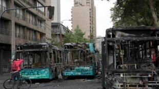 Um homem tira fotos de ônibus queimados, que foram destruídos durante o protesto do dia anterior contra o aumento dos preços das passagens de metrô em Santiago, Chile, em 20 de outubro de 2019.