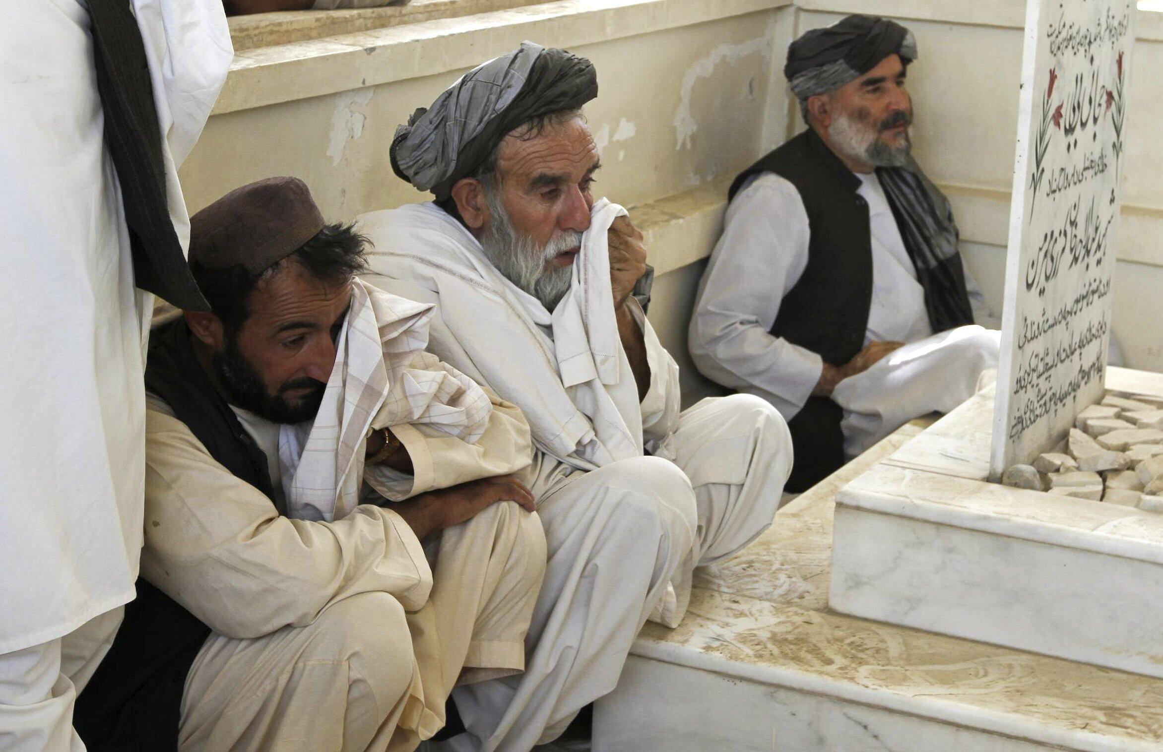 Afghans mourn at a grave yard after burying Ahmad Wali Karzai, President Hamid Karzai's brother who was killed by a bodyguard on Tuesday, in Kandahar province 13 July 2011