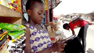 Une jeune fille effectue une demande en ligne de produits pour un magasin. Photo qui a reçu le prix du public lors du concours Photo eLearning Africa 2013.
