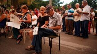 Cubanos consultam exemplar com texto da futura Constituição enquanto aguardam o início de um debate popular em Havana.
