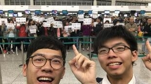 羅冠聰(左)和黃之鋒赴台交流前遇示威者,二人似未畏懼,還拍照留念。(羅冠聰臉書)