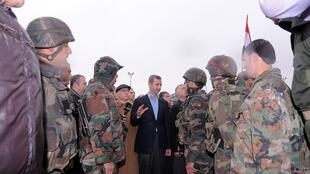 Syria's President Bashar al-Assad (C) speaks to soldiers during a tour in the Baba Amr neighbourhood of Homs