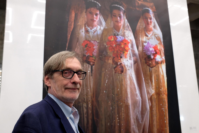 Jean-François Leroy devant une photo de Stephanie Sinclair dans la nouvelle Arche du photojournalisme sur la Grande Arche de la Défense, Paris.
