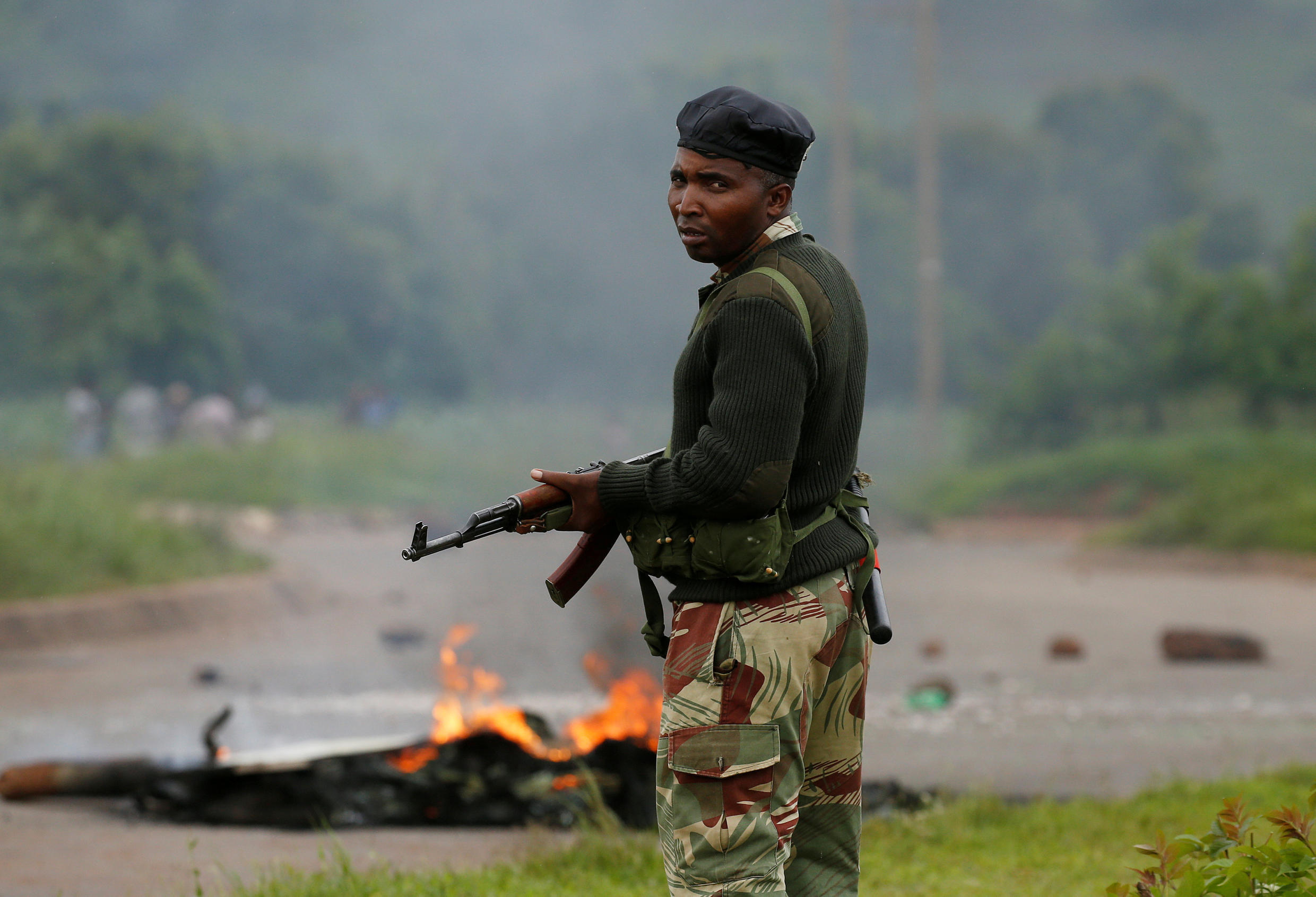 A soldier stands before a burning barricade during protests in Harare, Zimbabwe, January 15, 2019