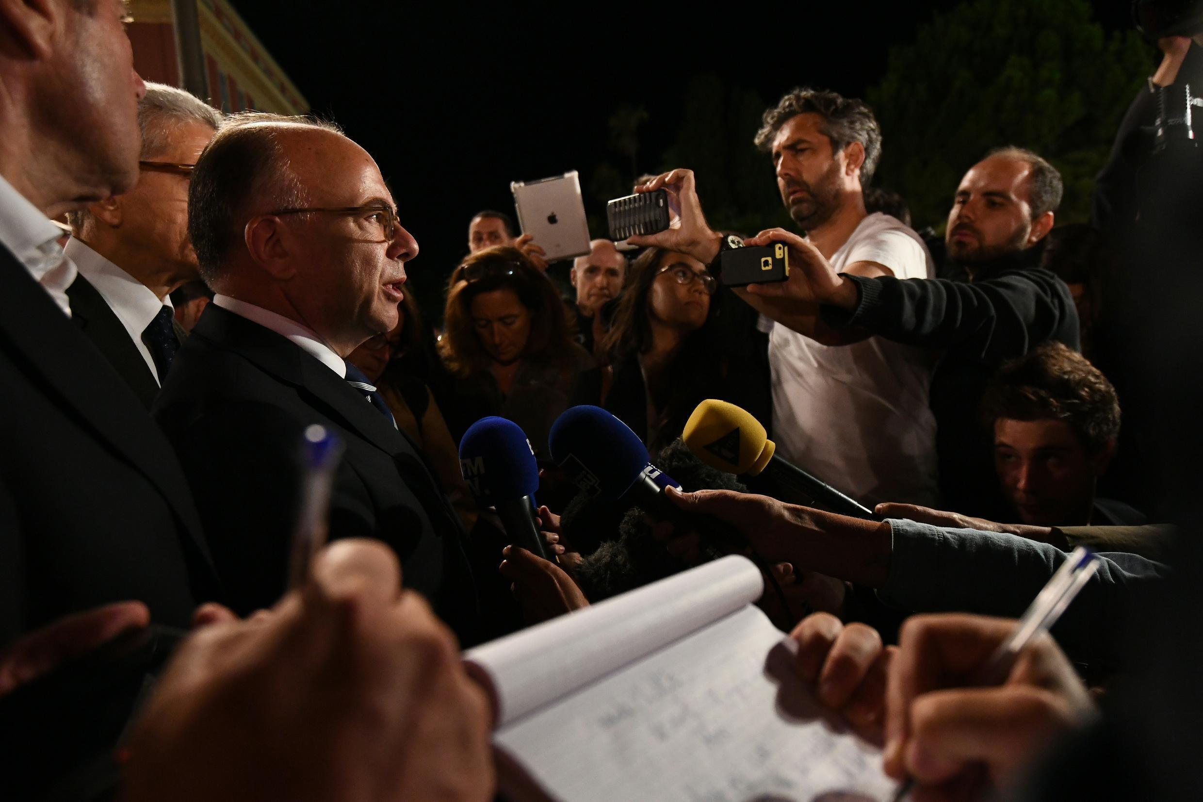French Interior Minister Bernard Cazeneuve (2nd L) speaks to the media in Nice early on Friday as he visits the area where a truck ploughed into a crowd of people during Bastille Day celebrations.